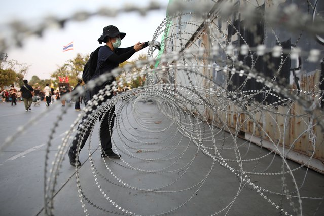 A person sets up barbed wire along containers blocking a road near the Grand Palace ahead of the anti-government protest, demanding resolutions of the government and reforms in the monarchy, in Bangkok, Thailand, March 20, 2021. (Photo by Soe Zeya Tun/Reuters)