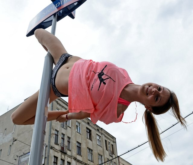"A member of the ""Avocadoo"" club performs a pole dance on a street sign pole in Lodz, central Poland on June 27, 2013. Talk about a traffic stopper: three pole dancers in central Poland have been honing their skills out in the streets, throwing their legs around signposts to the surprise and delight of many a passerby. (Photo by Janek Skarzynski/AFP Photo)"