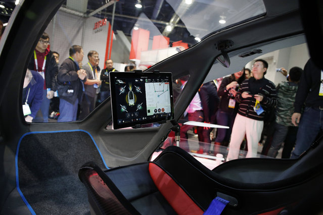 People crowd around the EHang 184 autonomous aerial vehicle at the EHang booth at CES International, Wednesday, January 6, 2016, in Las Vegas. (Photo by John Locher/AP Photo)