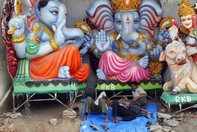 Indian artisans take a nap near idols of elephant-headed Hindu God Ganesha being prepared for Ganesh Chaturthi festival at a workshop in Hyderabad, India, Thursday, September 5, 2013. Ganesh Chaturthi, which begins from September 9, is celebrated as the birthday of Lord Ganesha who is widely worshiped by Hindus as the god of wisdom, prosperity and good fortune. (Photo by Mahesh Kumar A./AP Photo)
