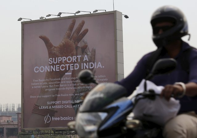 A motorist rides past a billboard displaying Facebook's Free Basics initiative in Mumbai, India, December 30, 2015. India has become a battleground over the right to unrestricted Internet access, with local tech start-ups joining the front line against Facebook Inc founder Mark Zuckerberg and his plan to roll out free Internet to the country's masses. The Indian government has ordered Facebook's Free Basics plan on hold while it decides what to do. (Photo by Danish Siddiqui/Reuters)