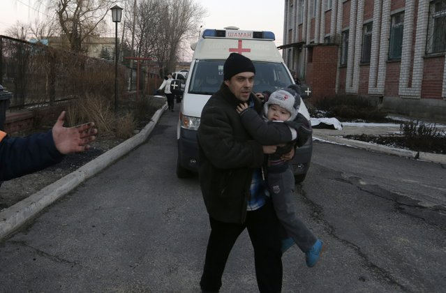 A man carries a child after shelling between Russian-backed separatists and Ukrainian government forces in a residential area of the town of Artemivsk, Ukraine, Friday, February 13, 2015. (Photo by Petr David Josek/AP Photo)