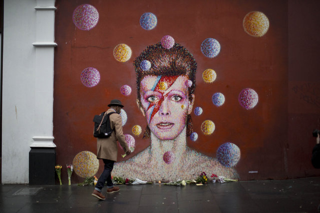 "A man walks to place flowers alongside other tributes beside a mural of British singer David Bowie by artist Jimmy C in Brixton, south London, Monday, January 11, 2016. David Bowie, the iconic and shape-shifting British singer whose illustrious career lasted five decade with hits like ""Fame,"" ''Heroes"" and ""Let's Dance,"" died Sunday after a battle with cancer. He was 69. The singer, who was born David Jones at the family home in the Brixton area of London, came of age in the glam rock era of the early 1970s. (Photo by Matt Dunham/AP Photo)"