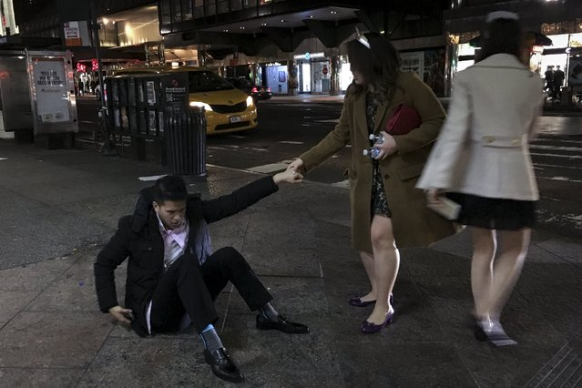 A woman helps her friend stand up after he had fallen to the ground following New Year's Eve celebrations in the Manhattan borough of New York, January 1, 2016. (Photo by Carlo Allegri/Reuters)