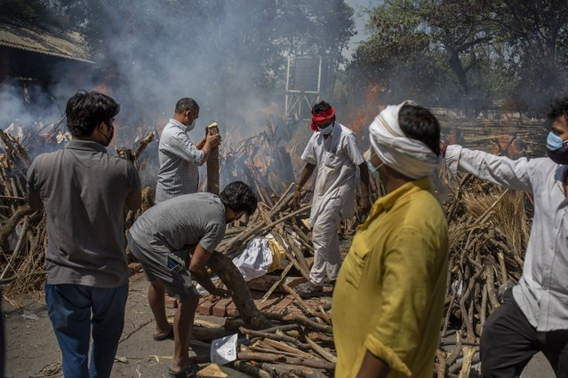 Members of a family of COVID-19 victim prepare funeral pyre for deceased member as multiple funeral pyres of those who died of COVID-19 are seen at a crematorium in New Delhi, India, Saturday, April 24, 2021. (Photo by Altaf Qadri/AP Photo)