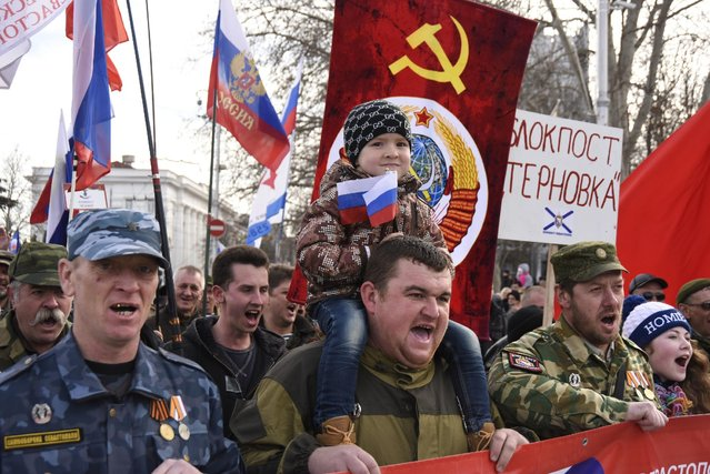 People, some of them dressed in military uniforms holding Russian and former Soviet Union flags attend a rally celebrating Defenders of the Fatherland Day in Sevastopol, Crimea, Monday, February 23, 2015. The Defenders of the Fatherland Day, celebrated in Russia and in Crimea on Feb. 23, honors the nation's military and is a nationwide holiday. (Photo by Alexander Polegenko/AP Photo)
