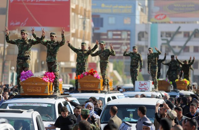 Members of a Shiite group, Asaib Ahl al-Haq, or League of the Righteous, flash victory signs during a funeral procession for six of their comrades who killed in Tikrit fighting Islamic militants, in Najaf, 100 miles (160 kilometers) south of Baghdad, Iraq, Thursday, March 5, 2015. Iranian-backed Shiite militias and Sunni tribes have joined Iraq's military in a major operation to retake Tikrit from the Islamic State group, while the U.S. led coalition has remained on the sidelines. (AP Photo/Jaber al-Helo)