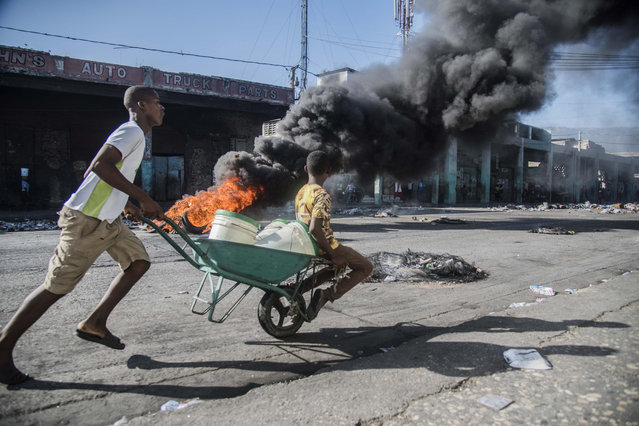 A man carries a child in a wheelbarrow near a burning tire barricade in the framework of the protests of the last three days due to the increase in fuel prices, in Port-au-Prince, Haiti, 09 July 2018. Haiti was today practically paralyzed by a transport strike after three days of violent riots due to an increase in fuel prices, which the Government left without effect shortly after the announcement. The Prime Minister, Jack Guy Lafontant, today heads a meeting with representatives of Parliament to assess the situation created after the violent protests, which have left at least three dead and several injured. (Photo by Jean Marc Hervé Abelard/EPA/EFE)