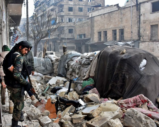 Syrian government forces walk in Aleppo's newly captured Al-Kalasseh neighbourhood in the eastern part of the war torn city on December 13, 2016. (Photo by George Ourfalian/AFP Photo)