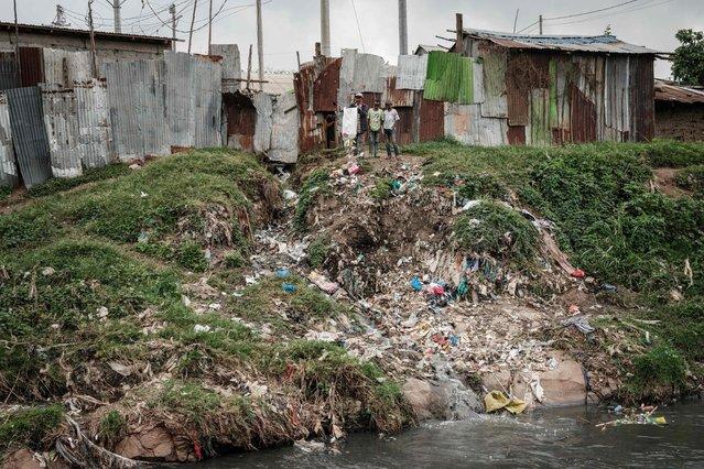 A man throws rubbish on the banks of the Nairobi River in Dandora slum in Nairobi on June 5, 2021, on World Environment Day. (Photo by Yasuyoshi Chiba/AFP Photo)