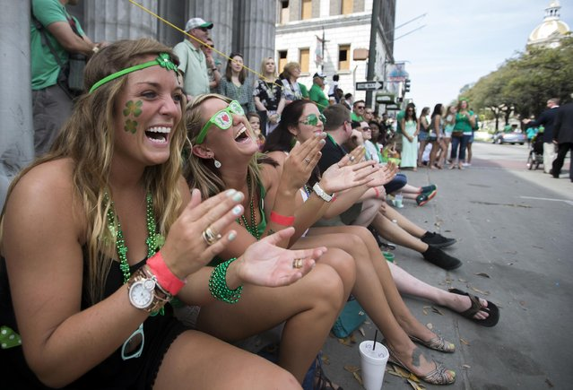 From left to right, Kelly Thompson, Shannon Davis and Michele Storey of Charleston, S.C., laugh and applaud a performance during the 191st St. Patrick's Day parade, Tuesday, March 17, 2015, in Savannah, Ga. The St. Patrick's Day tradition in Savannah dates back to the first parade held on March 17, 1824. (Photo by Stephen B. Morton/AP Photo)