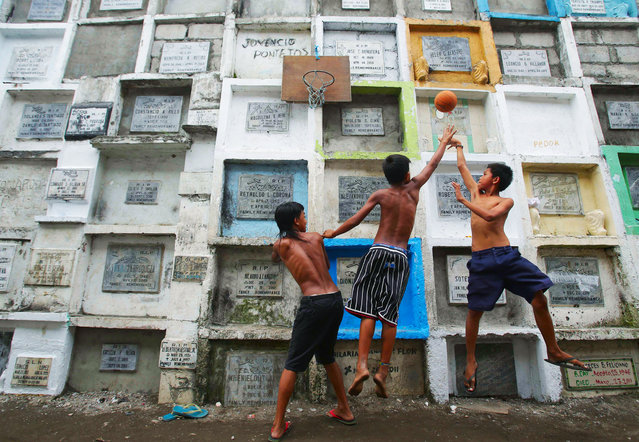 Filipino boys play basketball at an improvised court hooked on multi-layered tombs at a public cemetery in Navotas, north of Manila, Philippines on Thursday Oct. 31, 2013. Filipinos are expected to flock to cemeteries on November 1 to remember their dead as they observe All Saints Day in this predominantly Roman Catholic country. (Photo by Aaron Favila/AP Photo)