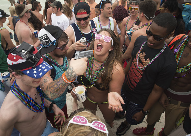 A squirt gun is used to spray alcohol into a party-goers mouth during spring break festivities in Panama City Beach, Florida March 12, 2015. (Photo by Michael Spooneybarger/Reuters)