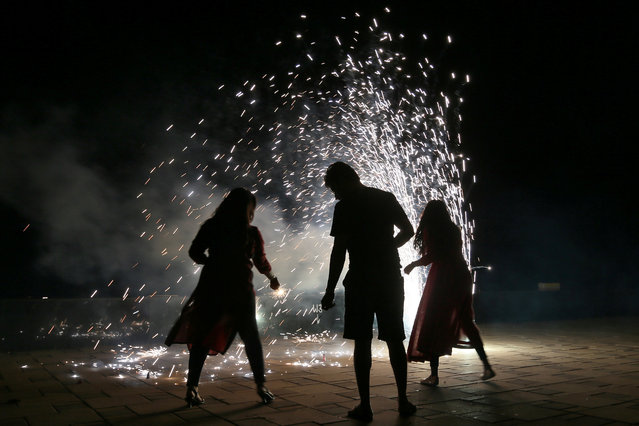 People light firecrackers on a street as they celebrate Diwali in Mumbai, India on November 7, 2018. (Photo by Francis Mascarenhas/Reuters)
