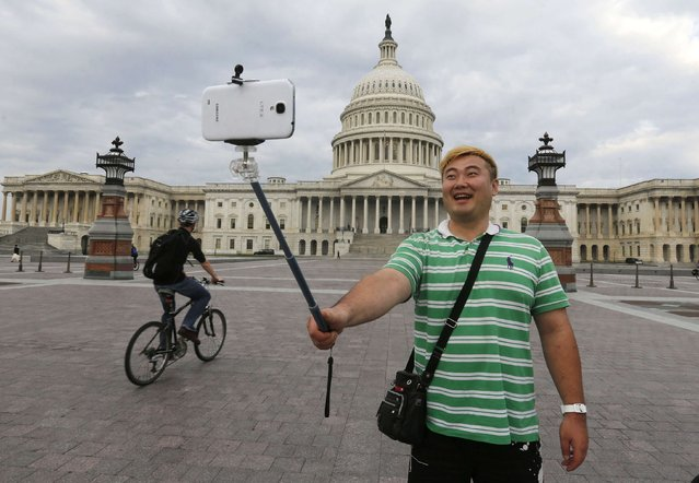 South Korean tourist Heemok Ann takes his own picture in front of the U.S. Capitol dome on Capitol Hill in Washington after the U.S. government shutdown, in this October 1, 2013 file photo. (Photo by Larry Downing/Reuters)