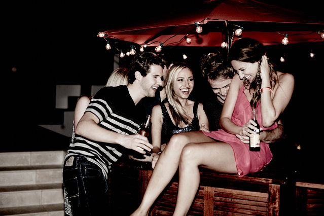 Young adult friends laughing together at night. (Photo by Robert Deutschman/Getty Images)