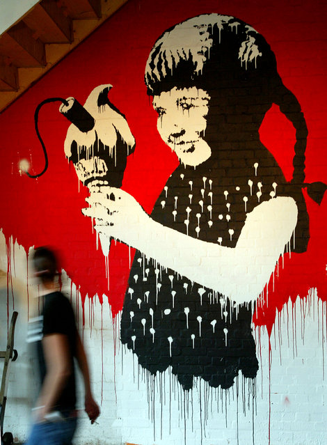 A Banksy painting of a young girl with a stick of dynamite in her ice cream on display at a London exhibtion in 2003. (Photo by Reuters/Stringer)