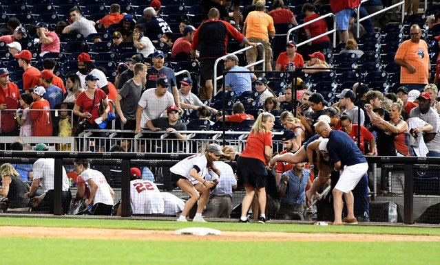 """People get up from their seats as they are asked to leave the Nationals Park stadium as the game between the Washington Nationals and the San Diego Padres was interrupted due to a shooting outside the stadium in Washington, DC, on July 17, 2021. Four people were shot outside a baseball stadium crowded with thousands of spectators in the US capital on Saturday, causing the game to be abruptly halted as spectators were ushered out. Police said four people had been shot but there was """"no ongoing threat"""", without clarifying the condition of the gunshot victims. (Photo by Ben Sheppard/AFP Photo)"""