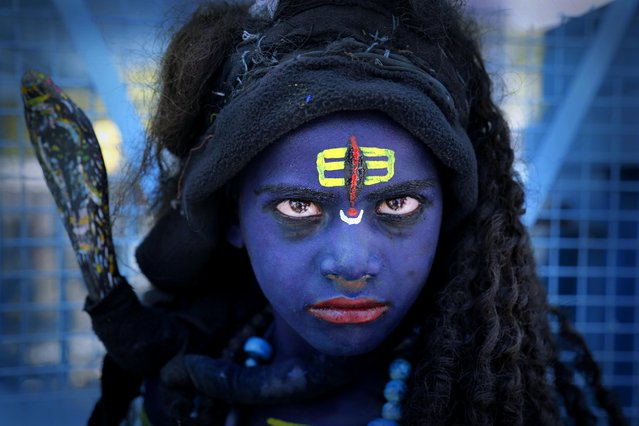 A young Indian boy dressed as Hindu God Shiva waits for alms from devotees on the occasion of Hanuman Jayanti festival in Ajmer, India, Friday, April 3, 2015. Hanuman Jayanti is celebrated as the birthday of the Hindu monkey-god Hanuman all over India. (Photo by Deepak Sharma/AP Photo)