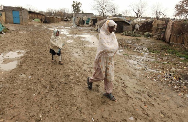 A woman and a girl walk on a muddy lane  on their way home in a slum on the outskirts of Islamabad February 16, 2015. (Photo by Faisal Mahmood/Reuters)