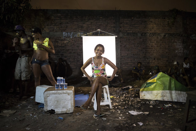 "In this March 18, 2015, photo, Carla Cristina, 26, poses for a portrait next to her water stand in an open-air crack cocaine market, known as a ""cracolandia"" or crackland, where users can buy crack, and smoke it in plain sight, day or night, in Rio de Janeiro, Brazil. Carla Cristina sells cups of water with an aluminum seal, which users will transform into makeshift pipes for smoking their crack. (Photo by Felipe Dana/AP Photo)"