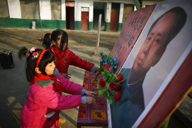 Students put plastic flowers next to a portrait of China's late chairman Mao Zedong at the Democracy Elementary and Middle School in Sitong town, Henan province December 4, 2013. (Photo by Carlos Barria/Reuters)