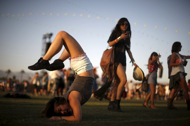 A woman does acrobatics as she waits for a band to start playing at the Coachella Valley Music and Arts Festival in Indio, California April 12, 2015. (Photo by Lucy Nicholson/Reuters)