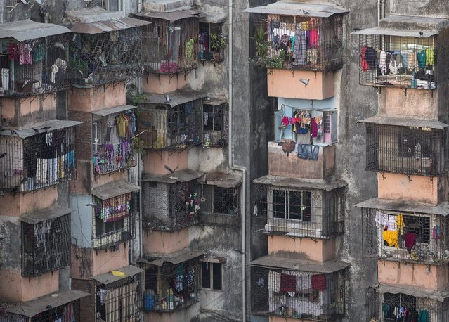 Windows of various apartments of a residential building are seen in Dharavi, one of Asia's largest slums, in Mumbai March 18, 2015. The cost for buying a 270 square feet (25 square meters) one-bedroom apartment in this building is around 11,850 Indian rupees ($190) per square feet or 3,200,000 Indian rupees ($ 51,175). The rent for an apartment in the same building is around 12,000 Indian rupees ($ 190) per month. (Photo by Danish Siddiqui/Reuters)