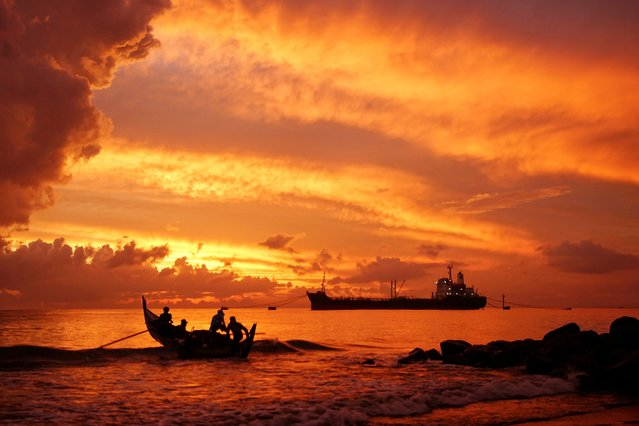 A fishing boat (L) heads out to sea at dawn in Lhokseumawe, Aceh on August 9, 2021. (Photo by Azwar Ipank/AFP Photo)