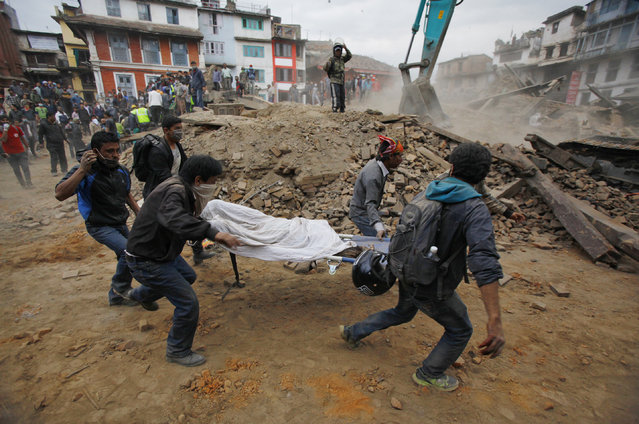 Volunteers carry the body of a victim on a stretcher, recovered from the debris of a building that collapsed after an earthquake  in Kathmandu, Nepal, Saturday, April 25, 2015. (Photo by Niranjan Shrestha/AP Photo)