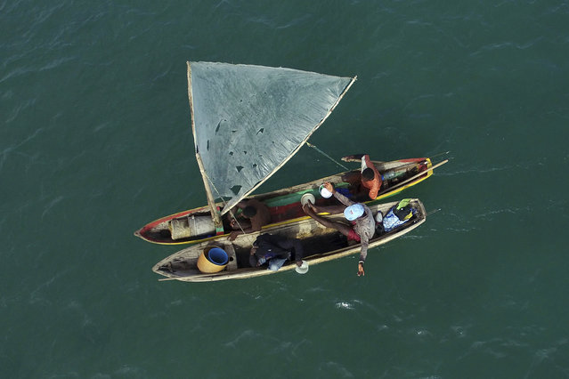 Fishermen sail their wooden boats in the bay of Port-au-Prince, Haiti, Wednesday, November 23, 2016. Haiti is the poorest nation in the hemisphere and one of the most unequal in the world, and with the depreciation of the currency, the gourde, the cost of living has risen sharply. (Photo by Ricardo Arduengo/AP Photo)