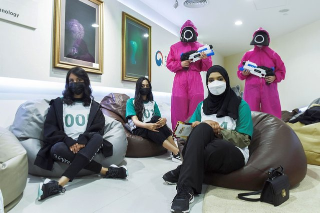 """Players pose for a photo as they are chosen to participate to play the real-life """"Squid game"""" at the Korean Cultural Center, in Abu Dhabi, United Arab Emirates, October 12, 2021. Hit South Korean show """"Squid Game"""" has officially become Netflix's biggest original series launch, the streaming service said. (Photo by Vidhyaa Chandramohan/Reuters)"""