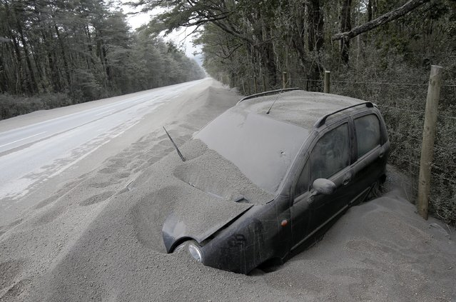 A vehicle covered with ashes remains off the road after the eruption of the Calbuco volcano, near the town of Ensenada, region of Los Lagos, in southern Chile, 26 April 2015. The National Service of Geology and Mining (SERNAGEOMIN, in Spanish) noted that until 25 April the Calbuco had expelled 210 million cubic meters of ash, that has forced 6,514 people to leave their homes due to the volcano activity. (Photo by Felipe Trueba/EPA)