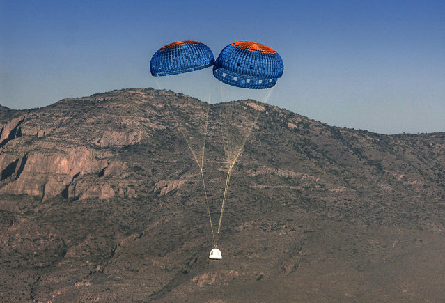 In this Thursday, April 29, 2015 photo provided by Blue Origin, the New Shepard crew capsule descends by parachute in the west Texas desert after separating from its propulsion module. (Photo by Blue Origin via AP Photo)
