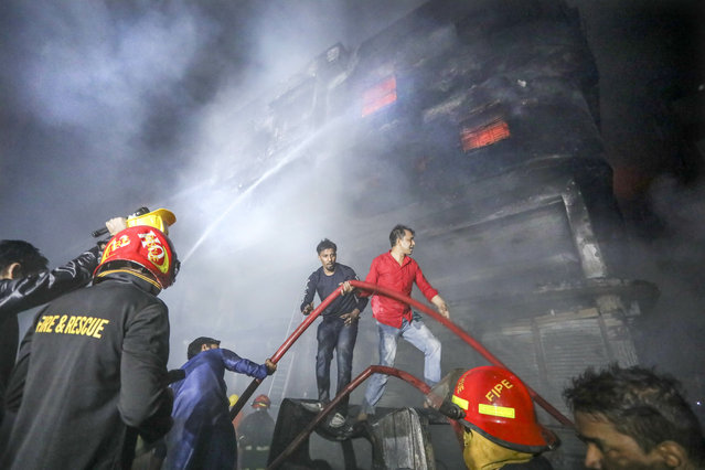 locals and firefighters douse flames of a smoldering fire in a building in Dhaka, Bangladesh, Thursday, February 21, 2019. The devastating fire raced through buildings in an old part of Bangladesh's capital and killed scores of people. (Photo by AP Photo/Stringer)