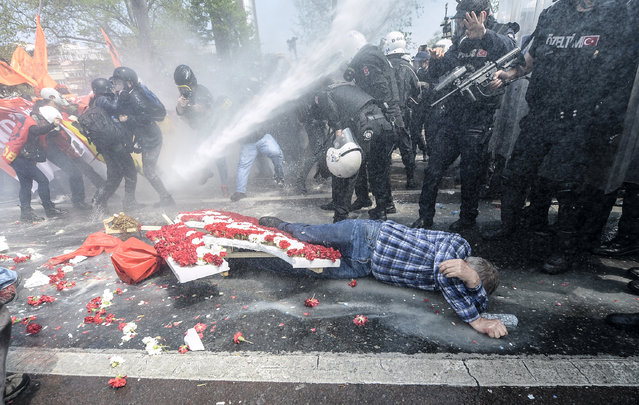A man lies on the ground as Turkish police use a water cannon to disperse protestors during a May Day rally near Taksim Square in Istanbul on May 1, 2015. Turkish police on used tear gas and water cannon to disperse protesters marking May Day in the Besiktas district of Istanbul as they tried to move towards the Taksim Square protest hub of Istanbul. (Photo by Bulent Kilic/AFP Photo)