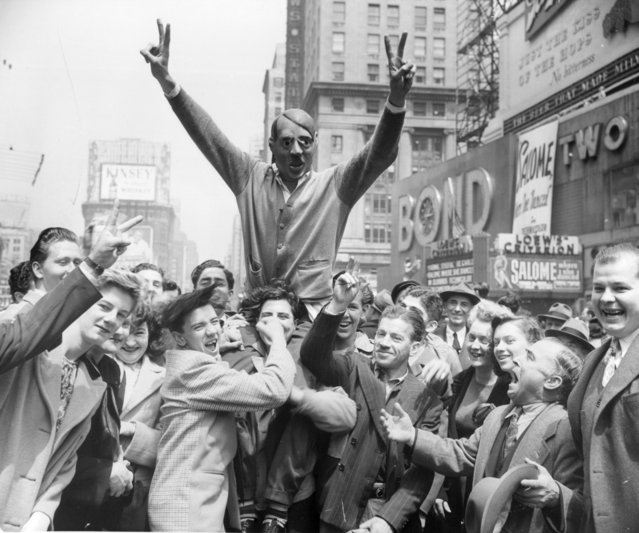 Cheering The News of Germany's Surrender New Yorkers Gather around a youth wearing a mask of Adolf Hitler to cheer the news of the Surrender of Germany on May 7. The Crowd is gathered in times Square, New York. May 08, 1945. (Photo by New York Post/Photo Archives, LLC via Getty Images)