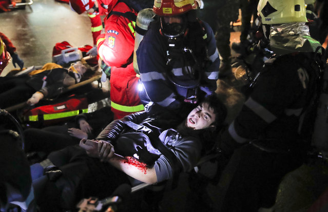 A volunteer posing as a victim grimaces while being evacuated from a subway station by emergency personnel during a rescue exercise in Bucharest, Romania, early Friday, April 12, 2019. NATO is holding a massive medical exercise in Romania, with over 2,500 medical personnel involved in responding to a simulated attack on the subway system of Bucharest, the Romanian capital. Dubbed Vigorous Warrior 2019. (Photo by Vadim Ghirda/AP Photo)