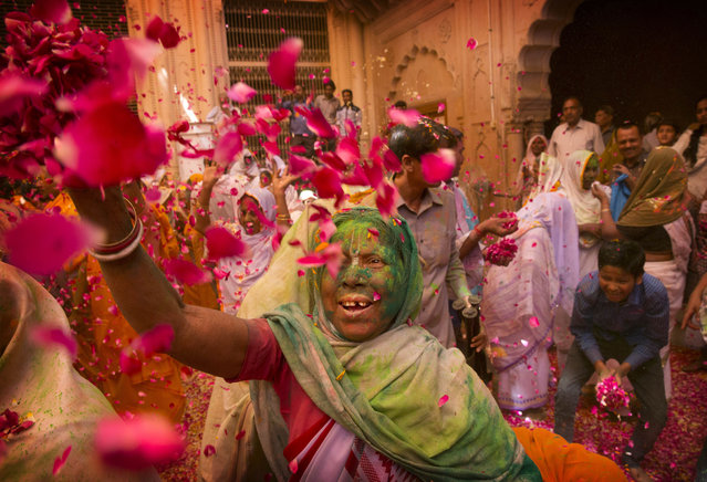 Indian Hindu widows throw flower petals and colored powder during Holi celebrations at the Gopinath temple, 180 kilometres (112 miles) south-east of New Delhi, India Monday, March 21, 2016. A few years ago this joyful celebration was forbidden for Hindu widows. Like hundreds of thousands of observant Hindu women they would have been expected to live out their days in quiet worship, dressed only in white, their very presence being considered inauspicious for all religious festivities. (Photo by Manish Swarup/AP Photo)