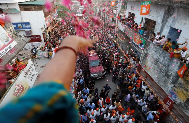 A supporter throws flower petals on India's Prime Minister Narendra Modi during a roadshow in Varanasi, India, April 25, 2019. (Photo by Adnan Abidi/Reuters)