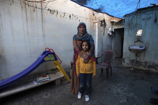 Bidaa Mhem Thabet al-Hasan (Um Suleiman), 39, poses with her daughter Mariam Khaled Masto, 9, outside their home in Deir al-Zor, Syria February 23, 2014. Bidaa is the director of a school founded by a group of teachers and volunteers. Her ambition was to become a gynaecologist. She hopes that her daughter will join the pharmacy school, but says that she will let her follow her own ambitions and that her success will make her happy. (Photo by Khalil Ashawi/Reuters)