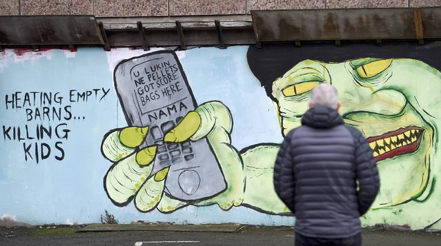 A man stops to look at a nationalist mural depicting Northern Ireland's First Minister Arlene Foster that refers to a flawed energy policy which has lead to deputy first minister Martin McGuinness resigning, throwing the devolved joint administration into jeopardy, in Belfast Northern Ireland, January 10, 2017. (Photo by Clodagh Kilcoyne/Reuters)