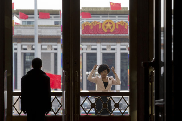 A television presenter adjusts her hair near a security person guarding the entrance to the Great Hall of the People where the closing ceremony of the Chinese People's Political Consultative Conference is held in Beijing, China, Wednesday, March 12, 2014. (Photo by Ng Han Guan/AP Photo)