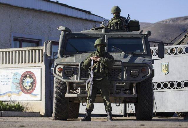 Armed men, believed to be Russian servicemen, stand guard outside a Ukrainian military base in Perevalnoye, near the Crimean city of Simferopol, March 19, 2014. Three Russian flags were flying at an entrance to Ukraine's naval headquarters in the Crimean port of Sevastopol on Wednesday, witnesses said, as pro-Russian forces took control of at least some of the base without armed resistance. (Photo by Shamil Zhumatov/Reuters)