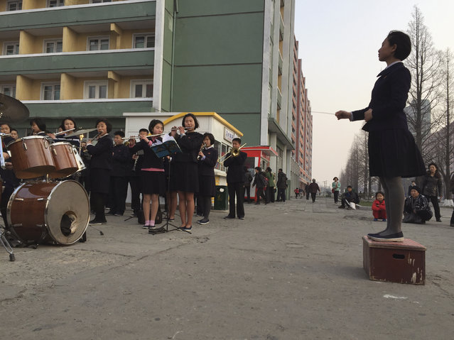 Schoolchildren play music to entertain and inspire people on their way home from work Tuesday, March 29, 2016 in Pyongyang, North Korea. North Korea has called a 70-day loyalty drive areas of a major congress of the ruling party scheduled for early May and everyone from students to coal miners have been mobilized nationwide to demonstrate their devotion to the leadership. (Photo by Eric Talmadge/AP Photo)