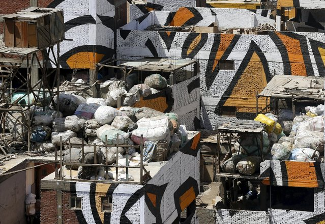 """Bags of garbage are left on the rooftop of a building, which makes up part of a mural painted on the walls of houses in Zaraeeb, created by French-Tunisian artist El Seed, in the shanty area known also as Zabaleen or """"Garbage City"""" on the Mokattam Hills in eastern Cairo, Egypt, April 4, 2016. (Photo by Amr Abdallah Dalsh/Reuters)"""