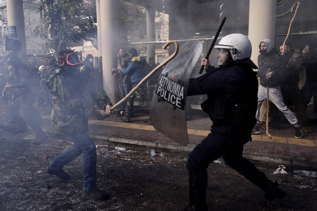 Greek farmers protesting higher taxes clash with riot police outside the Agriculture ministry in Athens, on March 8, 2017. Two people were detained after the windows of two police vans were smashed as approximately 1,000 farmers, mainly from the island of Crete, took part in the protest. (Photo by Louisa Gouliamaki/AFP Photo)
