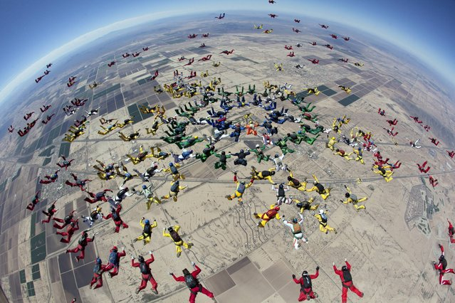 In this  Tuesday, April 1, 2014 photo provided by The World Team, a group of 222 skydivers from 28 nations, team members dive over Eloy, Ariz. The jump was part of the group's ongoing attempt to set a world record by forming two distinct aerial formations within the same dive. The team did not break the record with this attempt. (Photo by Andrey Veselov/AP Photo/World Team)