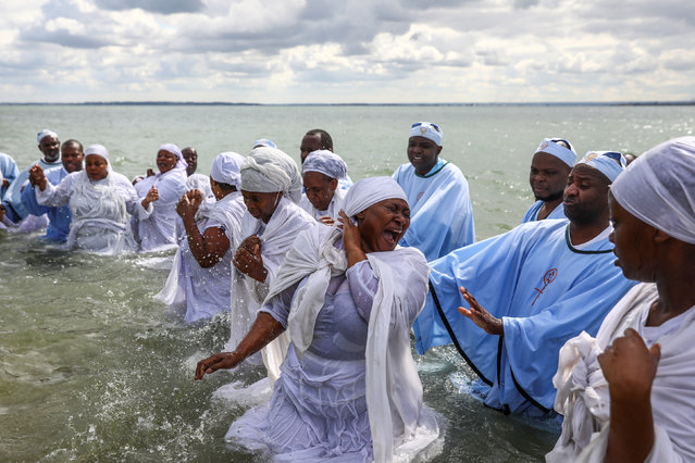 A woman reacts as senior members of the Apostles Of Muchinjikwa Christian church baptise members during a mass Baptism (Jorodhani) on the beachfront on Southend-on-Sea, Britain, August 25, 2018. Members of the church travel to Southend-on-Sea from all over the country, some from as far as Scotland, to join members from London, Leeds and Leicester for an annual ceremony. (Photo by Simon Dawson/Reuters)