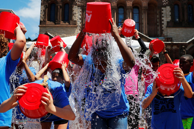 """Eleven-year-old Jahziyah Jones, with a crowd of others, pours a bucket of ice water over her head during an event to commemorate the five year anniversary of the """"ALS Ice Bucket Challenge"""", a viral activity started by Pete Frates and Pat Quinn to raise money for research into the ALS disease, in Boston, Massachusetts, U.S., July 15, 2019. (Photo by Brian Snyder/Reuters)"""